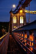 Full moon over the Menai Bridge at dusk.