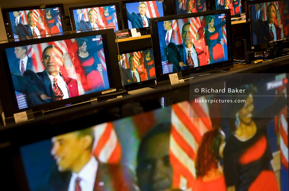 Live BBC news is being broadcast on TV screens in the John Lewis department store in Oxford Street, London, England. A newly-elected Barack Obama is seen woth his smiling wife Michelle and young family after speaking to his party faithful at a rally in Chicago the night of their election victory. Their faces merge together in a moment of television merging of images, large on the many home cinema screens seen across the world's media after this historic political election which saw the election of America's first black Commander in chief. The First Family have become household names and their lives  are about to change forever before they move into the White House. Obama speaks with passion about the changes he promises to bring to America while the rest of the world looks on hoping for new political directions.