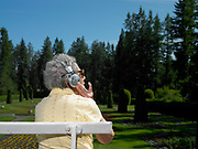 70 something female sitting on park bench listening to headphones