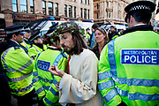 "Man dressed as Jesus walks through police lines at Occupy London protest at St Pauls, October 15th 2011. Protest spreads from the US with this demonstrations in London and other cities worldwide. The 'Occupy' movement is spreading via social media. After four weeks of focus on the Wall Street protest, the campaign against the global banking industry started in the UK this weekend, with the biggest event aiming to ""occupy"" the London Stock Exchange. The protests have been organised on social media pages that between them have picked up more than 15,000 followers. Campaigners gathered outside  at midday before marching the short distance to Paternoster Square, home of the Stock Exchange and other banks.It is one of a series of events planned around the UK as part of a global day of action, with 800-plus protests promised so far worldwide.Paternoster Square is a private development, giving police more powers to not allow protesters or activists inside."