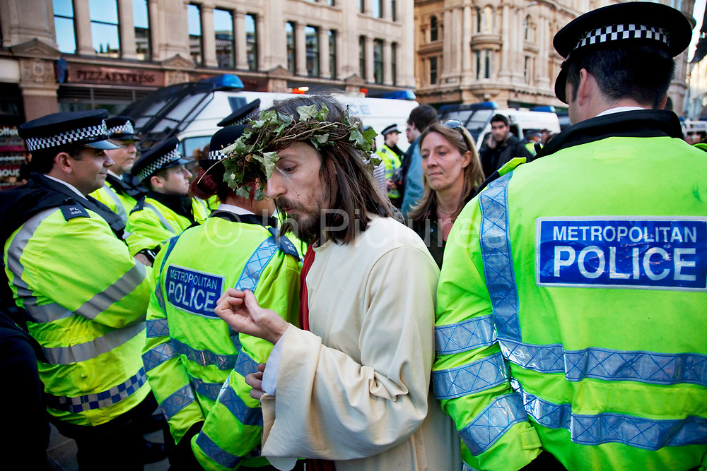 """Man dressed as Jesus walks through police lines at Occupy London protest at St Pauls, October 15th 2011. Protest spreads from the US with this demonstrations in London and other cities worldwide. The 'Occupy' movement is spreading via social media. After four weeks of focus on the Wall Street protest, the campaign against the global banking industry started in the UK this weekend, with the biggest event aiming to """"occupy"""" the London Stock Exchange. The protests have been organised on social media pages that between them have picked up more than 15,000 followers. Campaigners gathered outside  at midday before marching the short distance to Paternoster Square, home of the Stock Exchange and other banks.It is one of a series of events planned around the UK as part of a global day of action, with 800-plus protests promised so far worldwide.Paternoster Square is a private development, giving police more powers to not allow protesters or activists inside."""