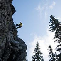 Chris Neve rappels at Rundle Rock near Banff, Alberta, in Canada's Banff National Park.