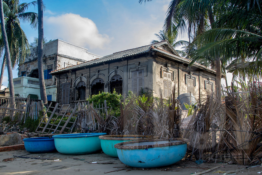Coracle boats in front of a deserted building along a beach in Mui Ne, Vietnam, Southeast Asia