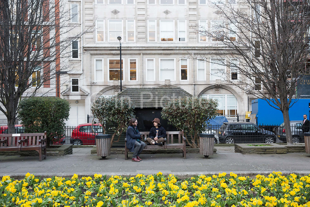 A couple sit on a park bench in Golden Square in Soho on the 23rd March 2018 in Central London in the United Kingdom.