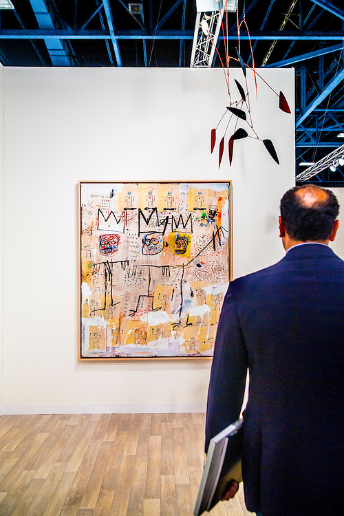 """Man views """"The Ruffians"""" by Jean-Michael Basquiat, 1982, arcrylic and oil paintstick and paper, at the Kukje Gallery, Seoul/ Tiny Kim Gallery, New York, at Art Basel Miami Beach 2012"""