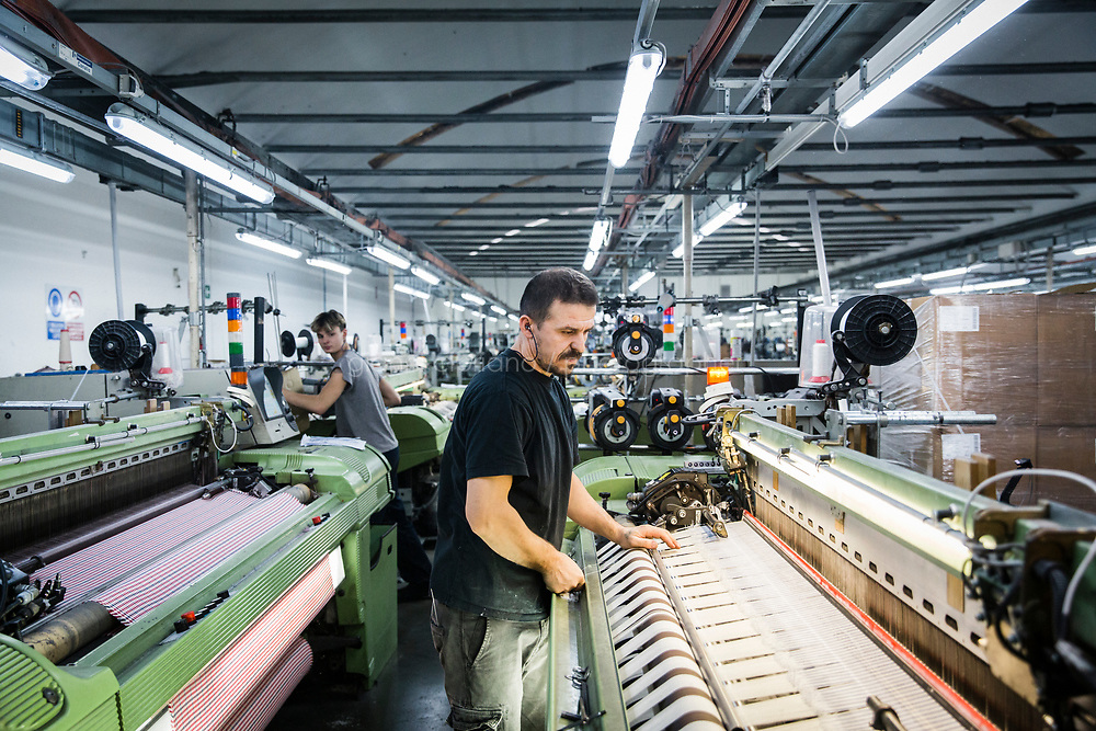 """PRATO, ITALY - 27 NOVEMBER 2019: A man is seen here at work in the Tronci textile factory, a supplier of Marini Industrie, in Prato, Italy, on November 27th 2019.<br /> <br /> Italy has proved especially vulnerable to China's emergence as a manufacturing juggernaut, given that many of its artisanal trades -- textiles, leather, shoe-making -- have long been dominated by small, family-run businesses that lacked the scale to compete on price with factories in a nation of 1.4 billion people. <br /> In recent years, four Italian regions that were as late as the 1980s electing Communists and then reliably supported center-left candidates -- Tuscany, Umbria, Marche and Emilia-Romagna  -- have swung dramatically to the extreme right. Many working class people say that delineation has it backwards: The left abandoned them, not the other way around. <br /> <br /> Between 2001 and 2011, Prato's 6,000 textile companies shrunk to 3,000, and those employed by the plants plunged from 40,000 to 19,000, according to Confindustria, the leading Italian industrial trade association. As Prato's factories went dark, people began arriving from China - mostly from the coastal city of Wenzhou, famed for its industriousness - to exploit an opportunity.<br /> They set up sewing machines across the concrete floors and imported fabric from factories in China. They sewed clothes, cannily imitating the styles of Italian fashion brands. They affixed a valuable label to their creations: """"Made In Italy""""."""