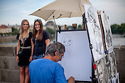 Two Prague visitors getting a painting (drawing) of themselves at Charles Bridge. Every artist working on Charles Bridge had to go through a selection process in front of a jury to get permission to work on the bridge.