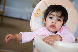 Young boy; sitting in a high chair; not very happy,