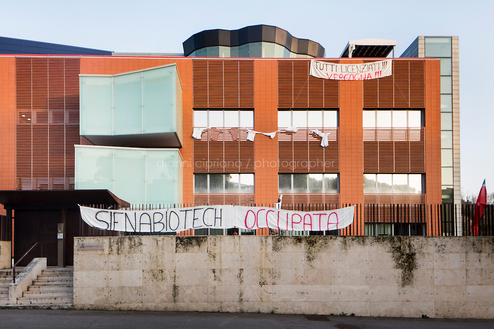 """SIENA, ITALY - 20 MARCH 2015: The headquarters of Siena Biotech, occupied by its 50 employees and researchers who protest against the financial cutback of the Monte dei Paschi di Siena Foundation, in Siena, Italy, on March 20th 2015. The banners set up on the gate and on the building say """"Siena Biotech Occupied"""" and """"All laid off!!! Shame on you!!!"""".<br /> <br /> Siena Biotech is a clinical-stage drug discovery company whose  efforts are mainly focused on discovering new drugs for therapeutic intervention against neurodegenerative diseases and in oncology, such as Alzheimer's Disease, Huntington's Disease and Cancer. Until 2014 Siena Biotech was entirely funded by the Monte dei Paschi di Siena Foundation.<br /> <br /> Now Siena Biotech has filed for bankruptcy proceedings, and its researchers and employees occupied the headquarters of the company based in Siena.<br /> <br /> Siena, a Tuscan city and UNESCO World Heritage Site, is home to Monte dei Paschi di Siena, the world's oldest surviving bank and Italy's third largest bank. The bank, founded in 1472, was the largest employer in Siena, and it helped finance a host of community projects and services until it stumbled during the financial crisis started in 2008."""