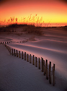 The sunset creates soft, warm light over a fence taken over through time by sand dunes