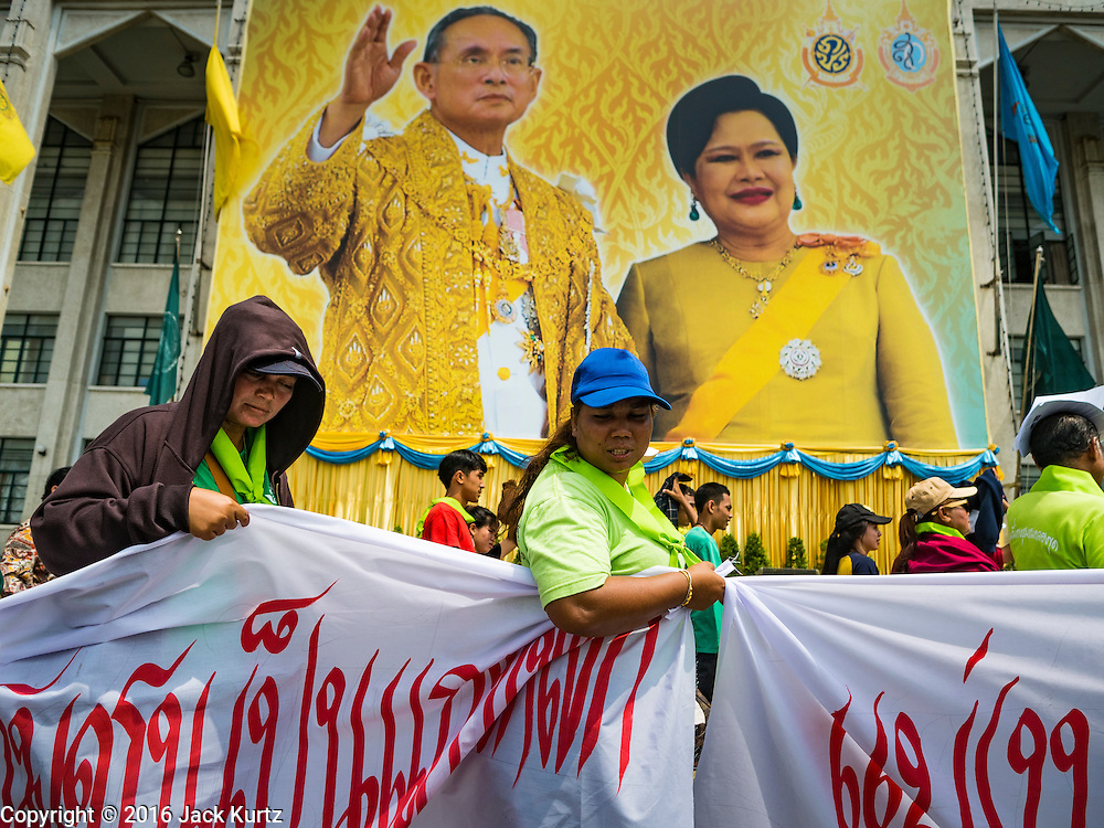 03 OCTOBER 2016 - BANGKOK, THAILAND:  World Habitat Day protesters pass a portrait of the Thai King and Queen in front of Bangkok city hall. In 1985, the UN General Assembly declared that World Habitat Day would be observed on the first Monday of October every year.  The declaration noted that every person deserves a decent place to live. In Bangkok this year, hundreds of people marched to the United Nations' offices to deliver a letter addressed to the UN Secretary General noting that forced evictions to facilitate urban renewal and gentrification was resulting in an increase in homelessness and substandard housing. Protesters and housing rights' activists also marched to the Prime Minister's Office and Bangkok city hall to express their concerns.     PHOTO BY JACK KURTZ