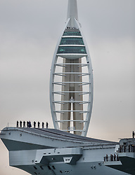 © Licensed to London News Pictures. 16/08/2017. Portsmouth, UK. The Royal Navy's new aircraft carrier HMS Queen Elizabeth passes the Spinnaker Tower as she enters her home port of Portsmouth for the first time. The new ship at 65,000 tonnes is the biggest warship ever built in the UK. Photo credit: Peter Macdiarmid/LNP