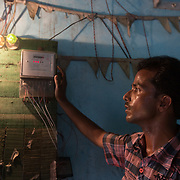CAPTION: Lathe owner Mujaheed, one of DESI Power's customers, checks his meter to see how much electricity he's consumed. LOCATION: Gayari, Araria District, Bihar, India. INDIVIDUAL(S) PHOTOGRAPHED: Mujaheed.