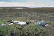 Abandoned derelict shabby sailing boat in marshland at Brancaster Staithe, Norfolk, UK