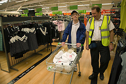 Day service user with learning disability out shopping at a supermarket with Care Assistant,