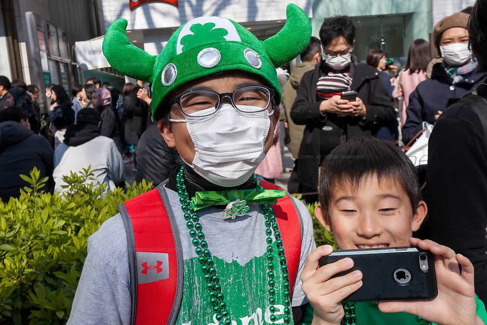 """Young Japanese boys  dressed in green enjoy the 27th Saint .Patrick's Day Parade in Omotesando, Tokyo, Japan. Sunday March 17th 2019. Started in 1992 by the Irish Network, Japan, and supported by the Embassy of Ireland,; the parade, along with the """"I Love Ireland Festival"""" held nearby is Asia's  largest Irish event."""