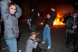 """© Licensed to London News Pictures;21/03/2021; Bristol, UK. Protestors watch and pose in front of a police van which has been set on fire as police clash with protesters outside New Bridewell Police Station on Sunday evening during a """"Kill the Bill"""" protest against Police, Crime, Sentencing and Courts Bill takes place through the centre of Bristol during the Covid-19 coronavirus pandemic in England. The Bill proposes new restrictions on protests. Lockdown restrictions have been partly lifted to allow people to gather outdoors socially in households, bubbles, or to meet one person from another household, but the police say protests are not allowed under the current Covid regulations. Photo credit: Simon Chapman/LNP."""