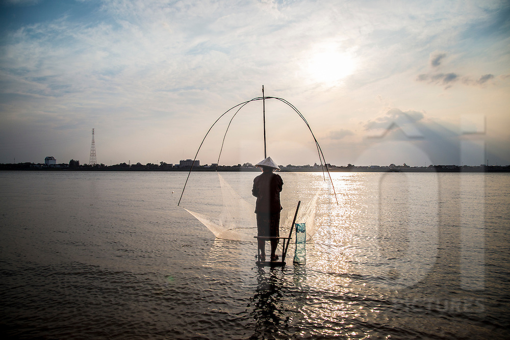 A lone woman fishes in the Mekong River in Thakhek, Laos, Southeast Asia