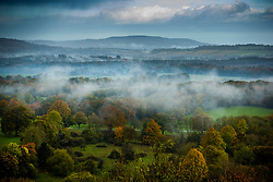 © Licensed to London News Pictures. 04/11/2019. Petworth, UK. Mist clings to autumnal trees in the South Downs National Park, south west of Petworth in West Sussex. Low pressure over the UK is bringing continued rain showers. Photo credit: Peter Macdiarmid/LNP