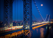 Moonrise as seen from Fort Lee, NJ as commuters cross over the George Washington Bridge. The George Washington Bridge, connecting New York City to Bergen County, NJ, is the worlds busiest suspension bridge.
