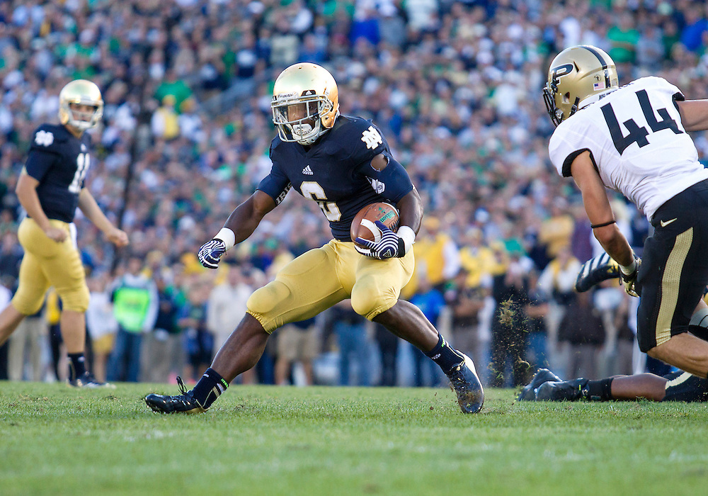 September 08, 2012:  Notre Dame Fighting Irish running back Theo Riddick (6) runs for the end one as Purdue safety Landon Feichter (44) defends during NCAA Football game action between the Notre Dame Fighting Irish and the Purdue Boilermakers at Notre Dame Stadium in South Bend, Indiana.  Notre Dame defeated Purdue 20-17.