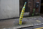 Bent over street lamp following a collision is wrapped in yellow warning tape in London, England, United Kingdom.
