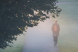 © Licensed to London News Pictures. 24/09/2018. London, UK.  A woman walks to work through heavy myst on a cold Autumn morning in Hyde Park, central London. Photo credit: Ben Cawthra/LNP