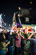 A woman stands atop a man's shoulder and reaches for a feathery item being lowered from a balcony above Bourbon Street.
