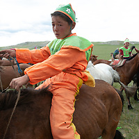 Young, costumed boys & girls - some bareback- after a 20km race at a traditional naadam festival on a remote pass in Arbulag Sum, near Muren in Hovsgol Aimag, Mongolia.