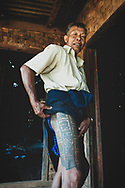 Kalaw, Myanmar - November 3, 2011: A Burmese man shows his tattooed thigh at his home in a village several miles outside Kalaw, located in Shan State.