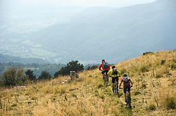 three mountain bikers on the way downhill, Matajur, Istria, Slovenia