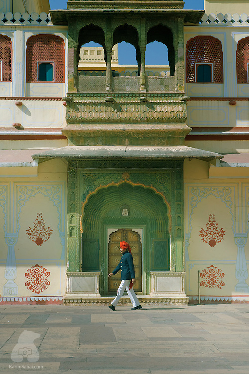 """A man wearing a red turban walks in the Pritam Niwas Chowk courtyard located inside the """"City Palace"""" in Jaipur, Rajasthan, India. The vast palatial complex, also known as """"Chandra Mahal"""", was built by Maharaja Sawai Jai Singh II -  the founder of the city of Jaipur - in the middle of the 18th century. The palace is one of the major touristic attractions of Jaipur."""