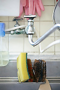 kitchen sink close up with various cleaning utensils