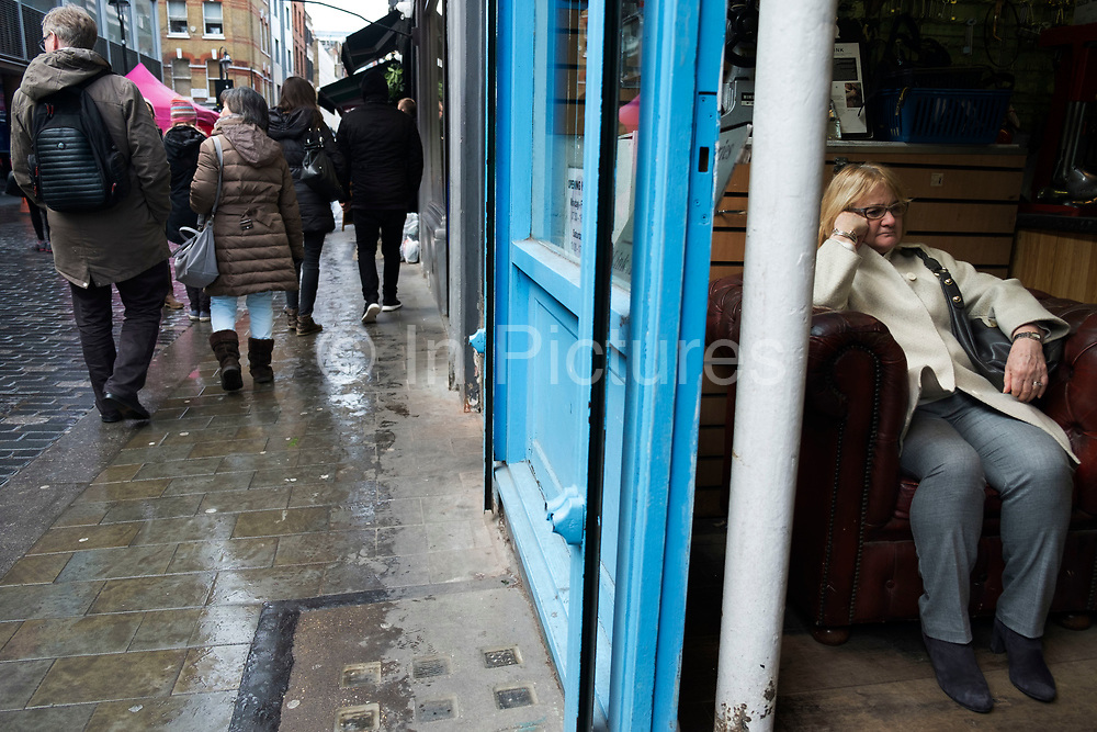 Bored woman waiting inside a shop on Berwick Street in Soho in London, England, United Kingdom.