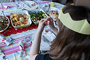 A young woman tries to solve a cracker novelty puzzle after a family lunch on Christmas Day, on 25th December 2020 in London, England. Christmas lunch or dinner in the UK is the main meal during the December Christian celebration, when families traditionally come together for the high-protein turkey and high-fibre vegetables - one of the most nutritious meals of the year.