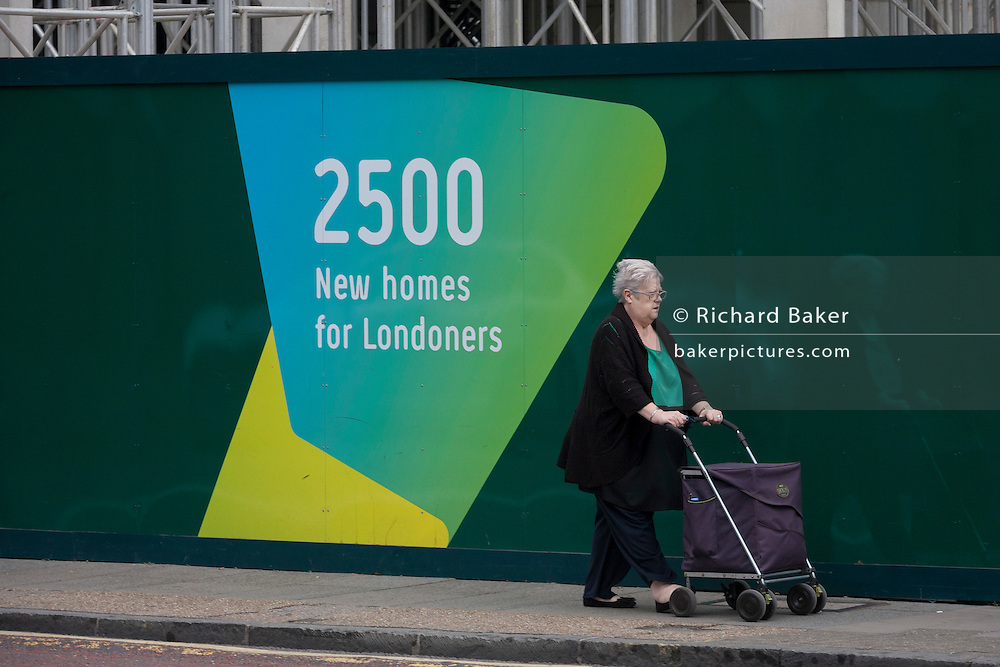 An elderly south Londoner walks past a regeneration project hoarding at Elephant Park, at Elephant & Castle, London borough of Southwark. Southwark Council's development partner, Lendlease is regenerating over 28 acres across three sites at the heart of Elephant & Castle, in what is the latest major regeneration opportunity in zone 1 London. The vision for the £1.5 billion regeneration is to build on the area's strengths and vibrant character in order to re-establish Elephant & Castle as one of London's most flourishing urban quarters. The Elephant & Castle regeneration is of a scale rarely seen in central London and includes almost 3,000 new homes, plus office, retail, community, leisure and restaurant space.