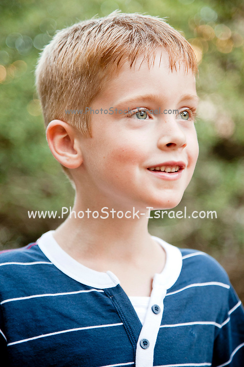 Portrait of a young red haired boy of seven outdoors