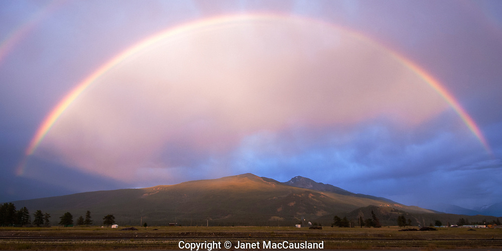 A Rainbow glows over Jasper train tracks and some Canadian Rocky Mountains.