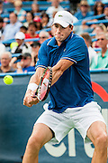 USA's John Isner his a return to Russia's Dmitry Tursunov during their men's semifinals singles match at the Citi Open ATP tennis tournament in Washington, DC, USA, 3 Aug 2013.  Tursunov won the first set 7-6 before play was suspended due to rain in the second set.