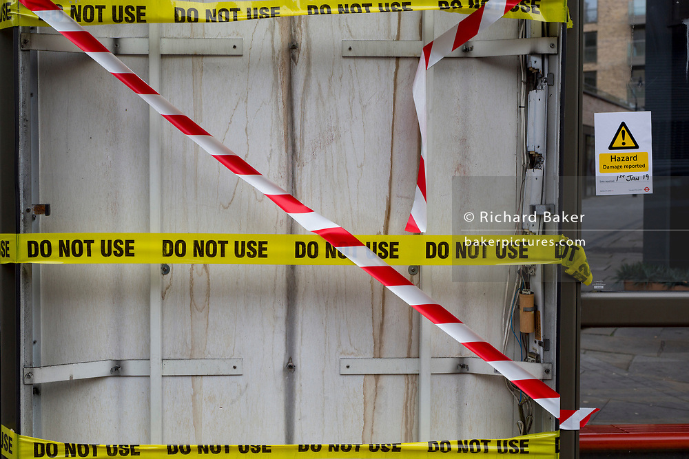 Striped hazard and Do Not Use tape is stretched across a smashed illuminated advertising panel at a bus stop shelter in Camberwell, on 11th January 2019, in Southwark, south London, England.