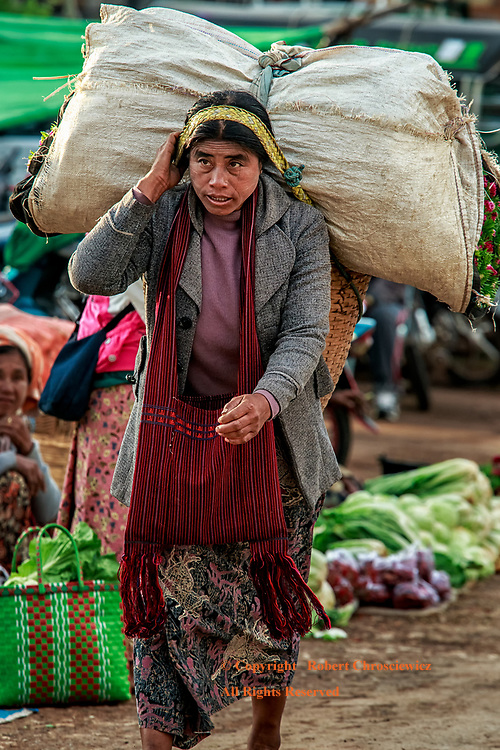 Kalaw Bundle:  A woman deftly negotiates the morning market, using a head band to carry both her filled woven basket and an over-sized bundle that rests on top, Kalaw Myanmar.