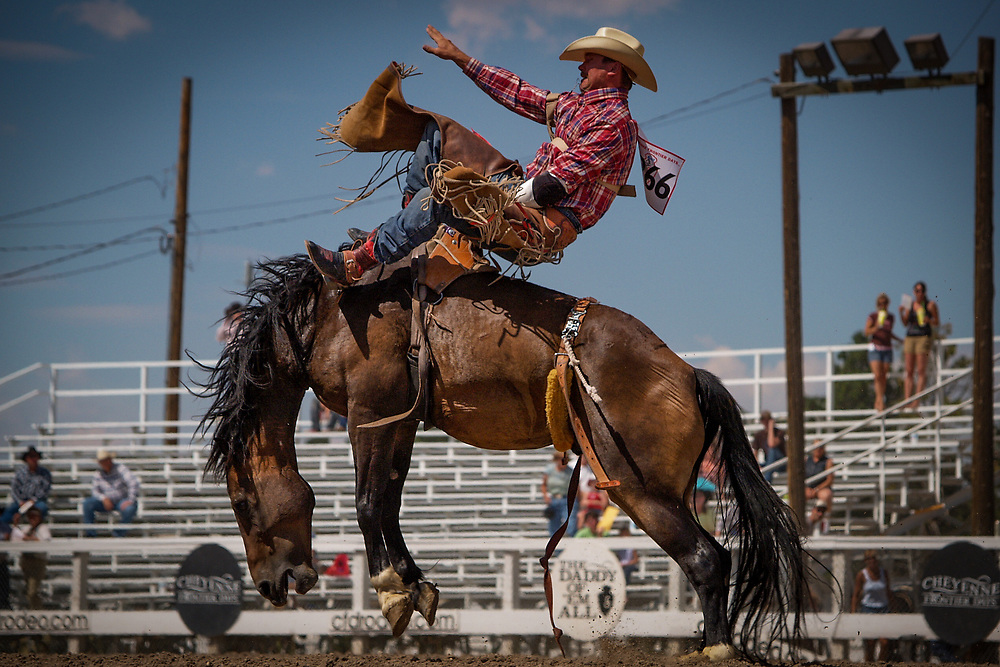 BEN WRZESINSKI of Boulder, Montana competes in the Bareback Riding event at the Cheyenne Frontier Days Rodeo,