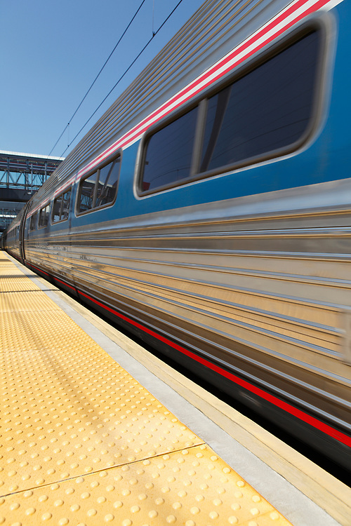 Wide angle view of a speeding commuter train traveling through a train station
