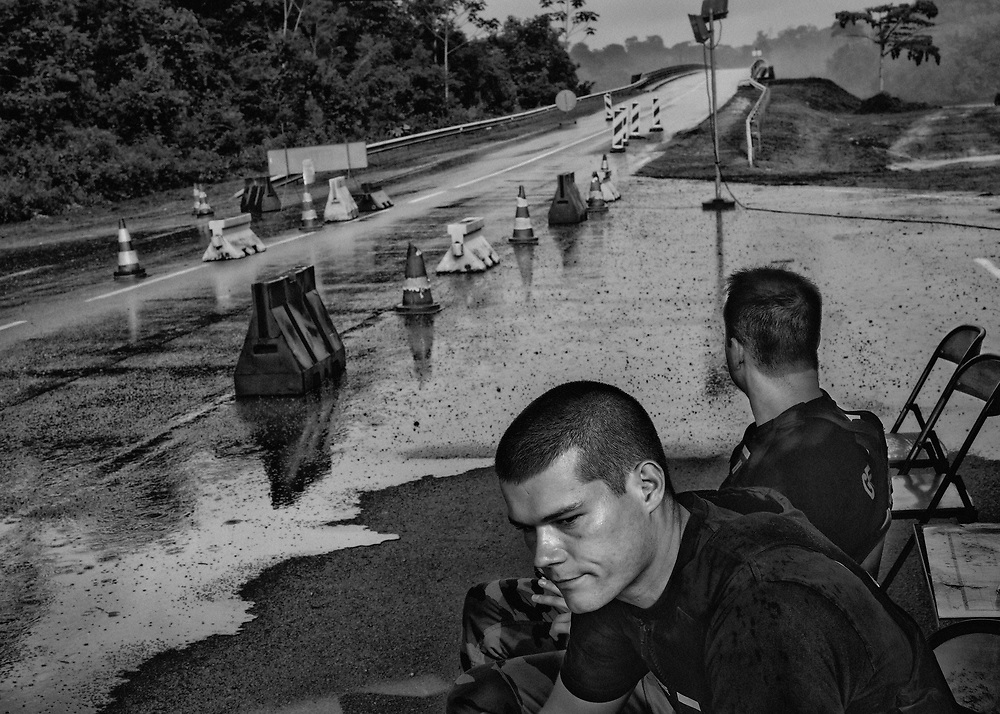 Pont de Régina, barrage militaire permanent, Guyane, 2015. <br /> <br /> Eldorado européen enclavé en Amazonie, la Guyane, avec son niveau de vie élevé, son système de couverture sociale et ses ressources naturelles, suscite l'intérêt des populations voisines. Dans un premier temps, la construction du centre spatial de Kourou a attiré une importante main d'œuvre clandestine et depuis le début des années 2000, l'envol du cours de l'or entraine un afflux massif de garimpeiros illégaux depuis le Suriname ou le Brésil. <br /> <br /> Le gouvernement français tente de réagir à cette perte de souveraineté nationale sur le territoire guyanais. Depuis 2002, les services de la police, des douanes, de la gendarmerie et de la légion sont associés dans des opérations coordonnées ; 350 militaires et 200 gendarmes sont aujourd'hui déployés sur les réseaux fluviaux ou en forêt pour démanteler les sites d'orpaillage illégaux. <br /> <br /> Depuis 2000, le préfet de Guyane prend une succession d'arrêtés décrétant l'établissement de postes fixes de gendarmerie aux fins de contrôles de police administrative. La prorogation répétée de l'arrêté institue la mise en place de barrages permanents et permet des contrôles d'identité systématiques. <br /> <br /> Depuis mars 2013, le barrage militaire permanent de Bélizon a été déplacé sur le pont de Régina, proche de la frontière brésilienne. Un second barrage est en fonction à Iracoubo, dans l'Ouest guyanais à proximité de la frontière Surinamaise. <br /> <br /> Les passeurs s'adaptent à cette nouvelle situation et s'organisent. Pour rejoindre Cayenne par la mer, la pirogue part dans la soirée d'Oiapoque sur la rive brésilienne et arrive sur le Mahury le lendemain soir, coût : 90 euros. Par la forêt, c'est un peu plus cher. Il faut compter 150 euros jusqu'à Cayenne, 200 euros pour Kourou et 250 euros pour Saint-Laurent. Les passeurs font monter les clandestins en voiture à Saint-Georges, les déposent quelques kilomètres avant le barrage de gen