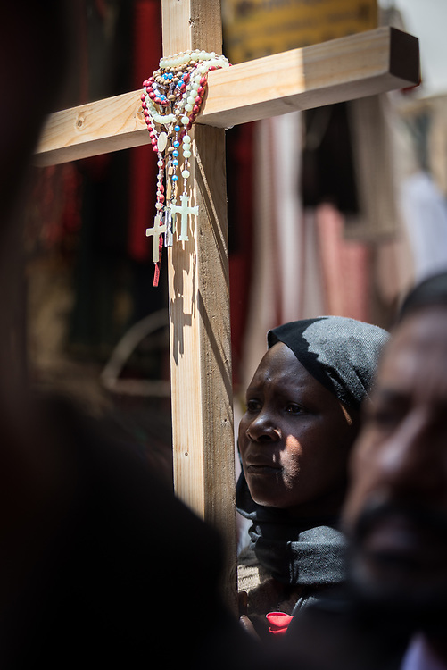 19 April 2019, Jerusalem: A woman holds a cross, as thousands of Christians march the Via Dolorosa on Good Friday, marking the stations of the cross in the Jerusalem Old City, in memory of the path Jesus walked carrying his cross towards his crucifixion.