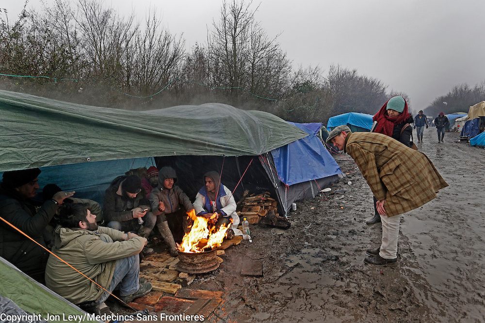 Refugees huddle around a fire to keep warm in heavy rain and freezing temperatures in the refugee camp in Grande Synthe, Dunkirk: <br /><br />Grande Synthe, Dunkirk: A Gill visits the refugee camps of Calais and Grande Synthe in Dunkirk.