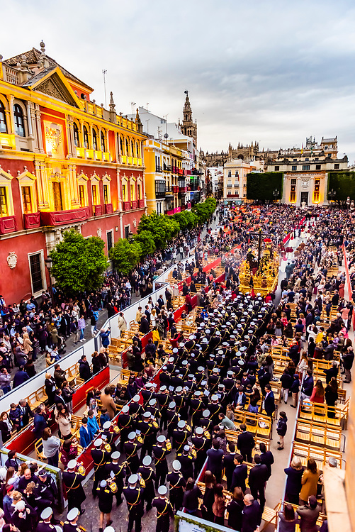 A paso (float) of the crucifixion of Jesus Christ followed by a marching band in the procession of the Brotherhood (Hermandad) La Lanzada enters Plaza San Francisco, Holy Week (Semana Santa), Seville, Andalusia, Spain.
