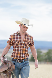rugged cowboy holding a saddle on a ranch