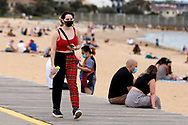 A woman walks along St Kilda Beach during COVID-19 in Melbourne, Australia. Premier Daniel Andrews comes down hard on Victorians breaching COVID 19 restrictions, threatening to close beaches if locals continue to flout the rules. This comes as Victoria sees single digit new cases. (Photo by Dave Hewison/Speed Media)