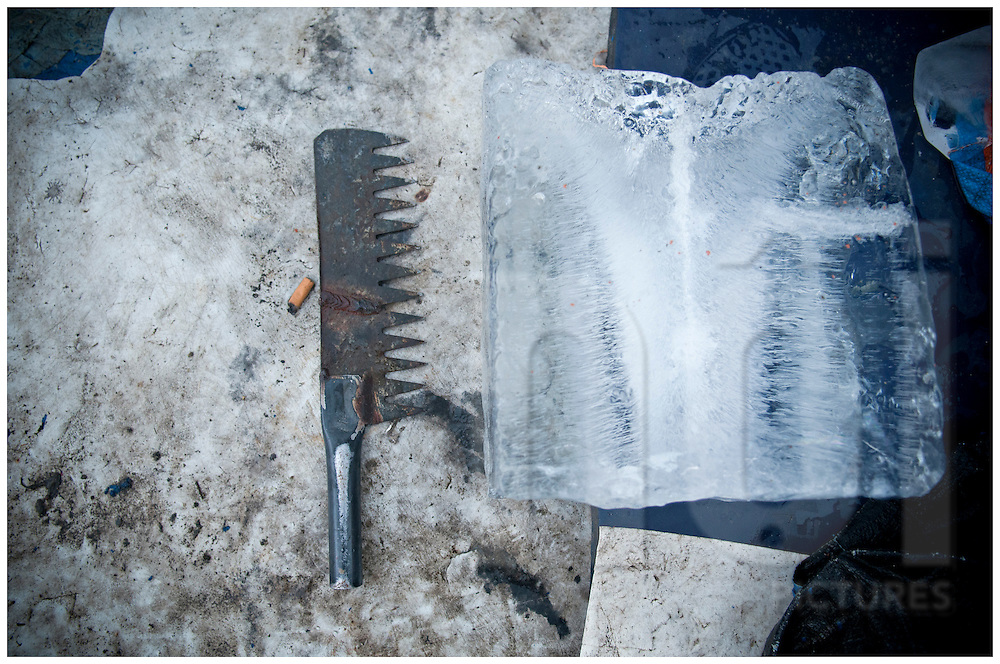 Big piece of ice with a rudimentary serrated knife on the side. Doc Let harbour, Vietnam, Asia
